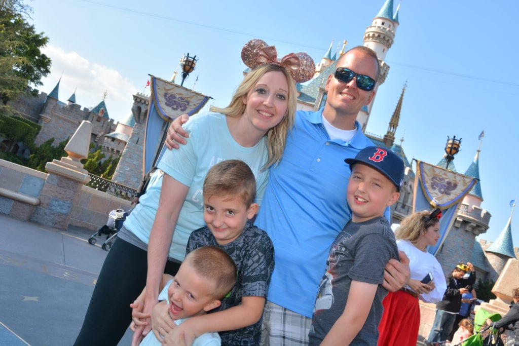 A family standing outside Sleeping Beauty's Castle at Disneyland.