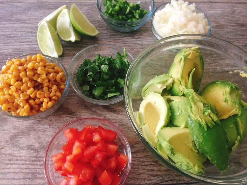 Ingredients for Chunky Guacamole. A bowl of corn, a bowl chopped tomatoes, a bowl of chopped jalapeños, a bowl of diced onions, fresh lime wedges, and a bowl of avocados.