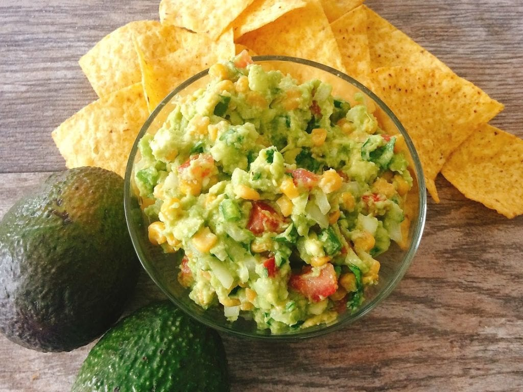A bowl of Fully-Loaded Chunky Guacamole surrounded by tortilla chips and an avocado.