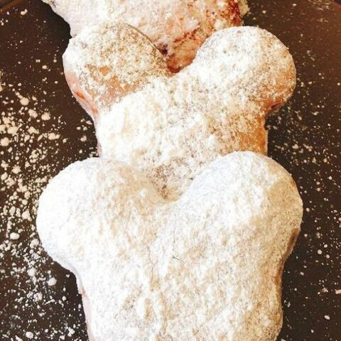 Three homemade Mickey Mouse shaped beignets covered in powdered sugar