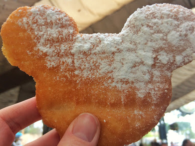 A hand holding up a Mickey Beignet at Disneyland