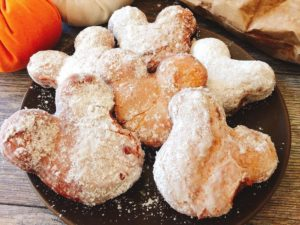 A plate full of Mickey Mouse shaped beignets, covered in powdered sugar.