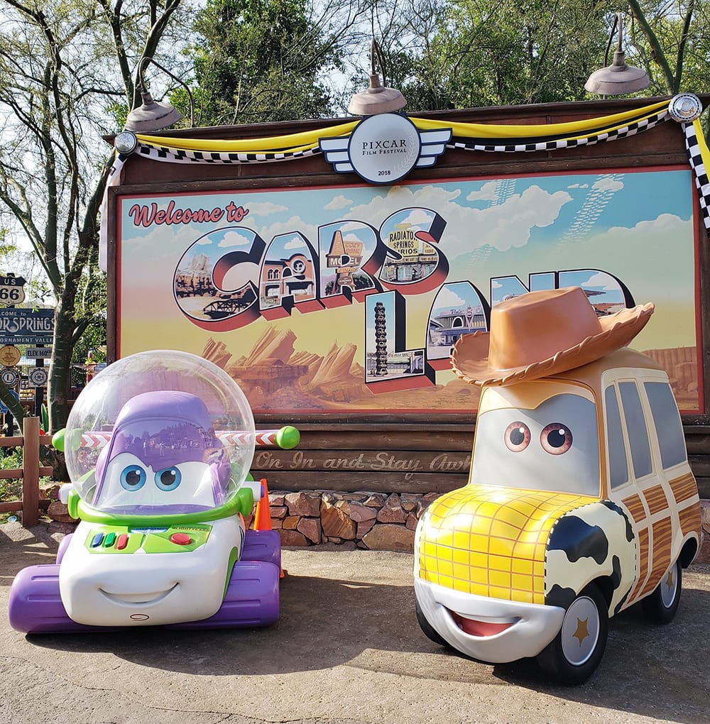 Woody and Buzz Lightyear cars in front of Cars Land Sign