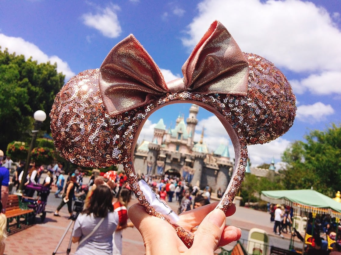 A pair of Rose Gold Minnie Mouse Ears in front of Sleeping Beauty's Castle at Disneyland