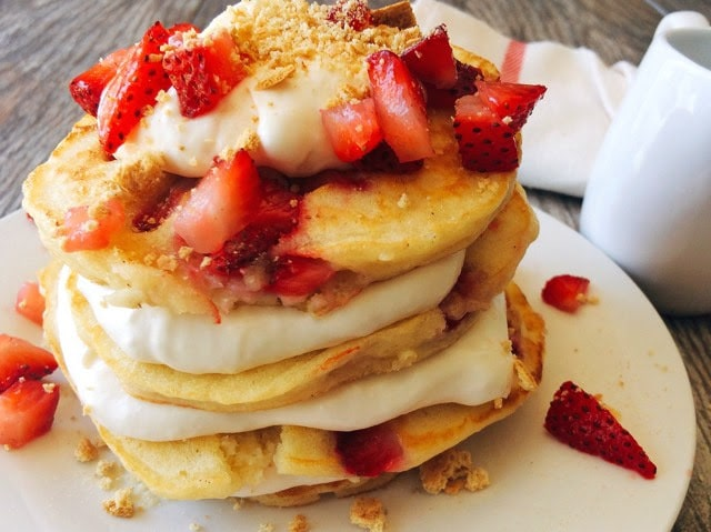A stack Strawberry Cheesecake Pancakes sprinkled with chopped strawberries and layered with Cheesecake Topping on a white plate with a syrup cup and a kitchen towel in the background.