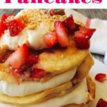 "A stack Strawberry Cheesecake Pancakes sprinkled with chopped strawberries and layered with Cheesecake Topping on a white plate with a syrup cup and a kitchen towel in the background. Text ""Strawberry Cheesecake Pancakes""."