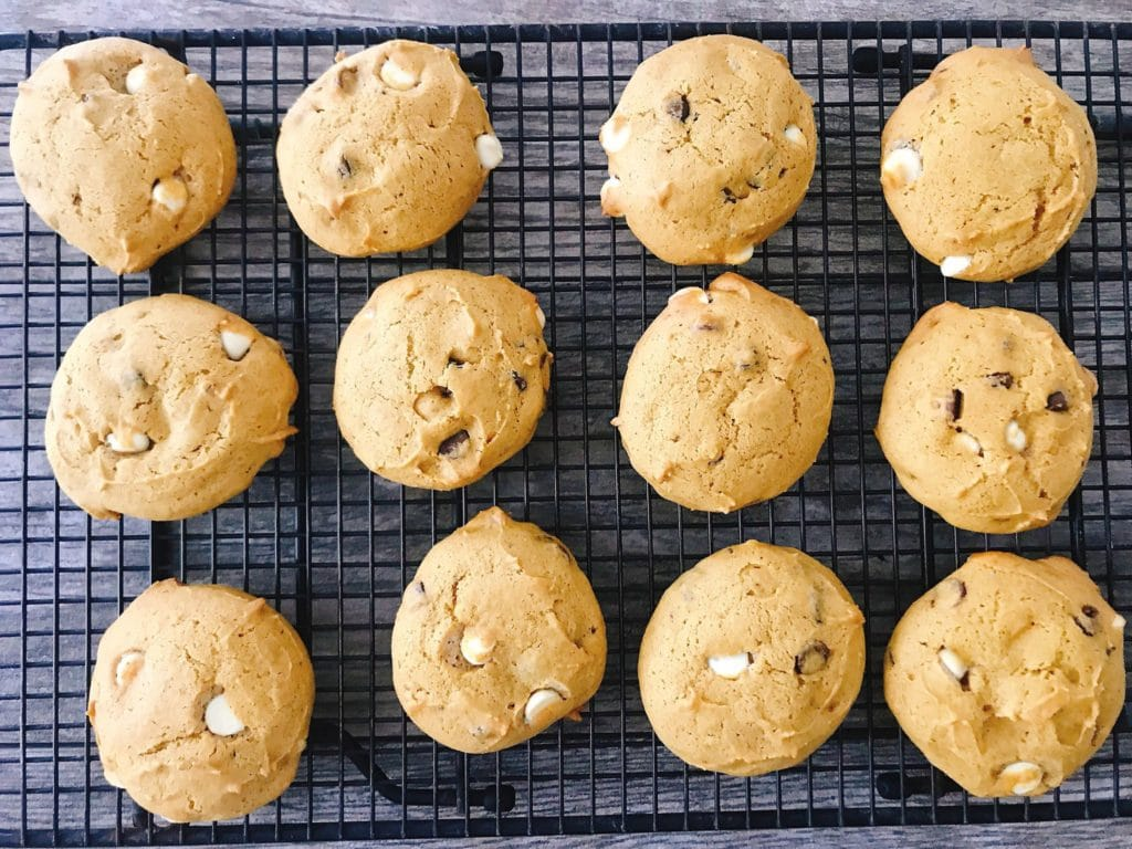 Soft white chocolate chip cookies on a cooling rack.