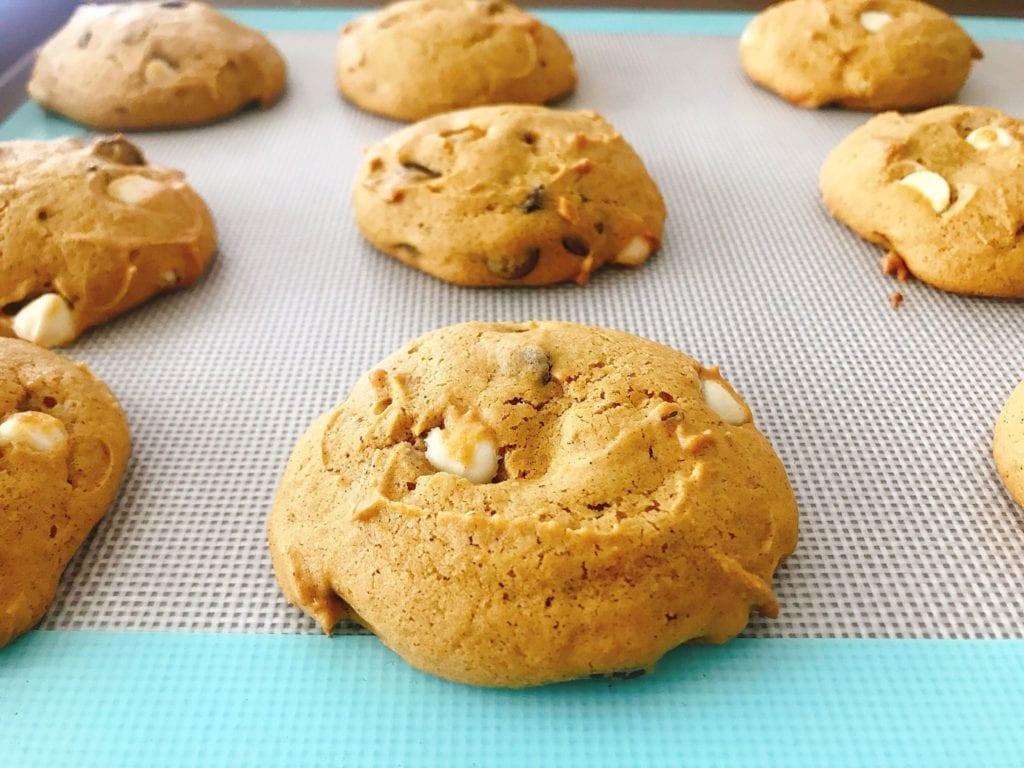 A close up of soft pumpkin chocolate chip cookies on a baking sheet.