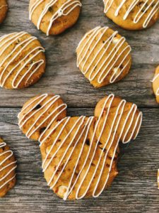 A Mickey Mouse shaped Soft Pumpkin Chocolate Chip Cookie drizzled with white chocolate.