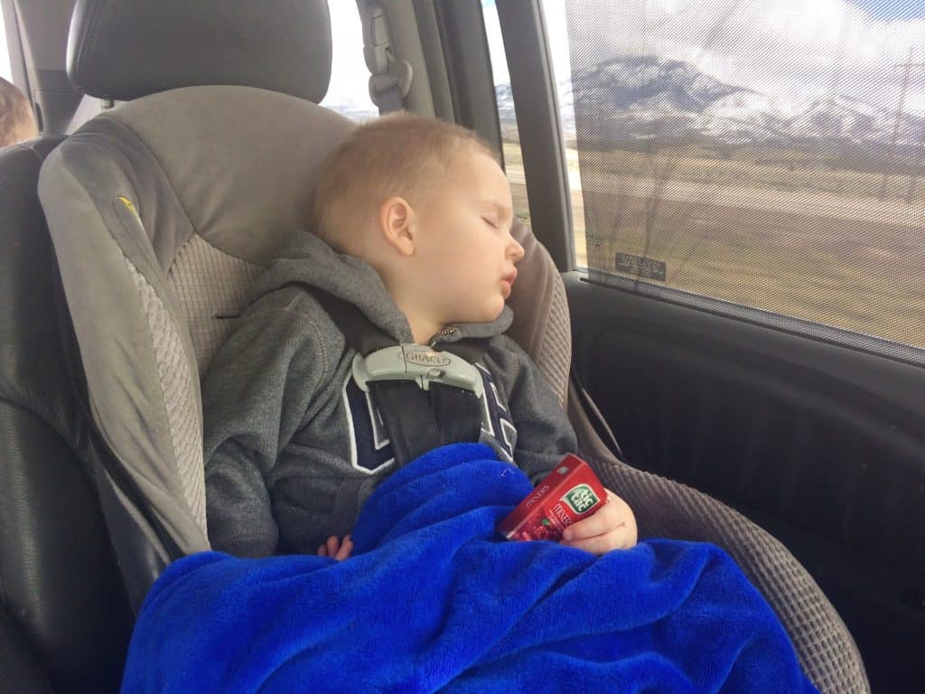 A toddler asleep in a car seat