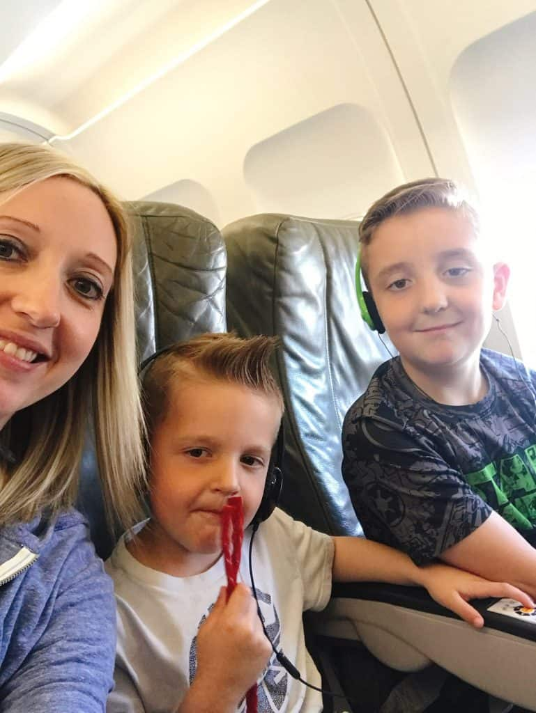 A woman and two kids sitting inside an airplane.