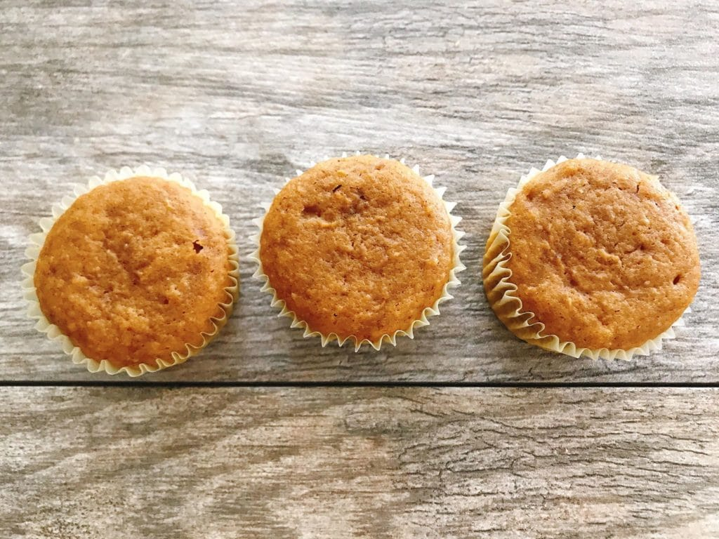 Three pumpkin spice cupcakes on a wood background to make Halloween Cupcakes.