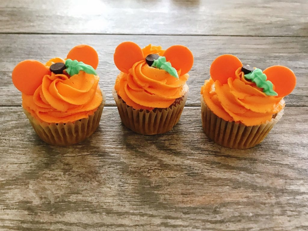 Three cupcakes decorated with orange frosting and orange candy melts to look like a Mickey Mouse Pumpkin to make Halloween Cupcakes.