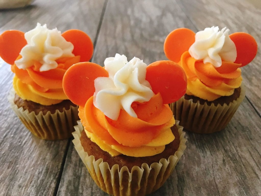Three cupcakes decorated to look like Mickey candy corn Halloween Cupcakes.