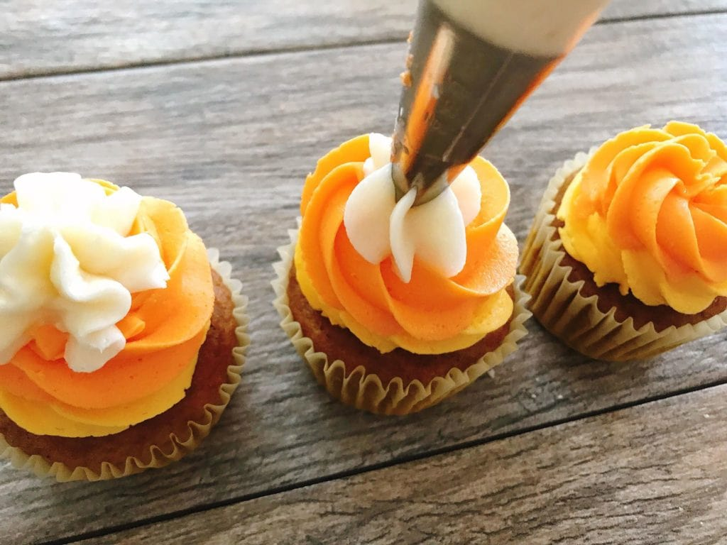 A piping bag piping a star on top of a candy corn cupcake to make Halloween Cupcakes.