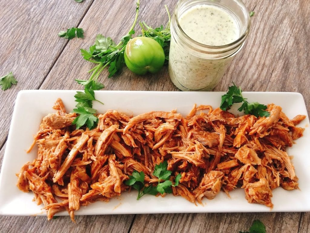 A plate of pulled Sweet Pork Barbacoa sprinkled with cilantro with a jar of creamy cilantro lime ranch.