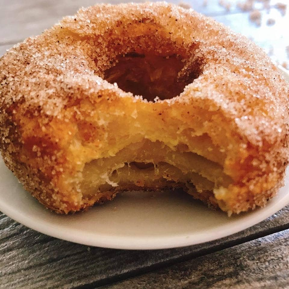 A freshly fried Disney World cronut on a white plate covered in cinnamon and sugar.