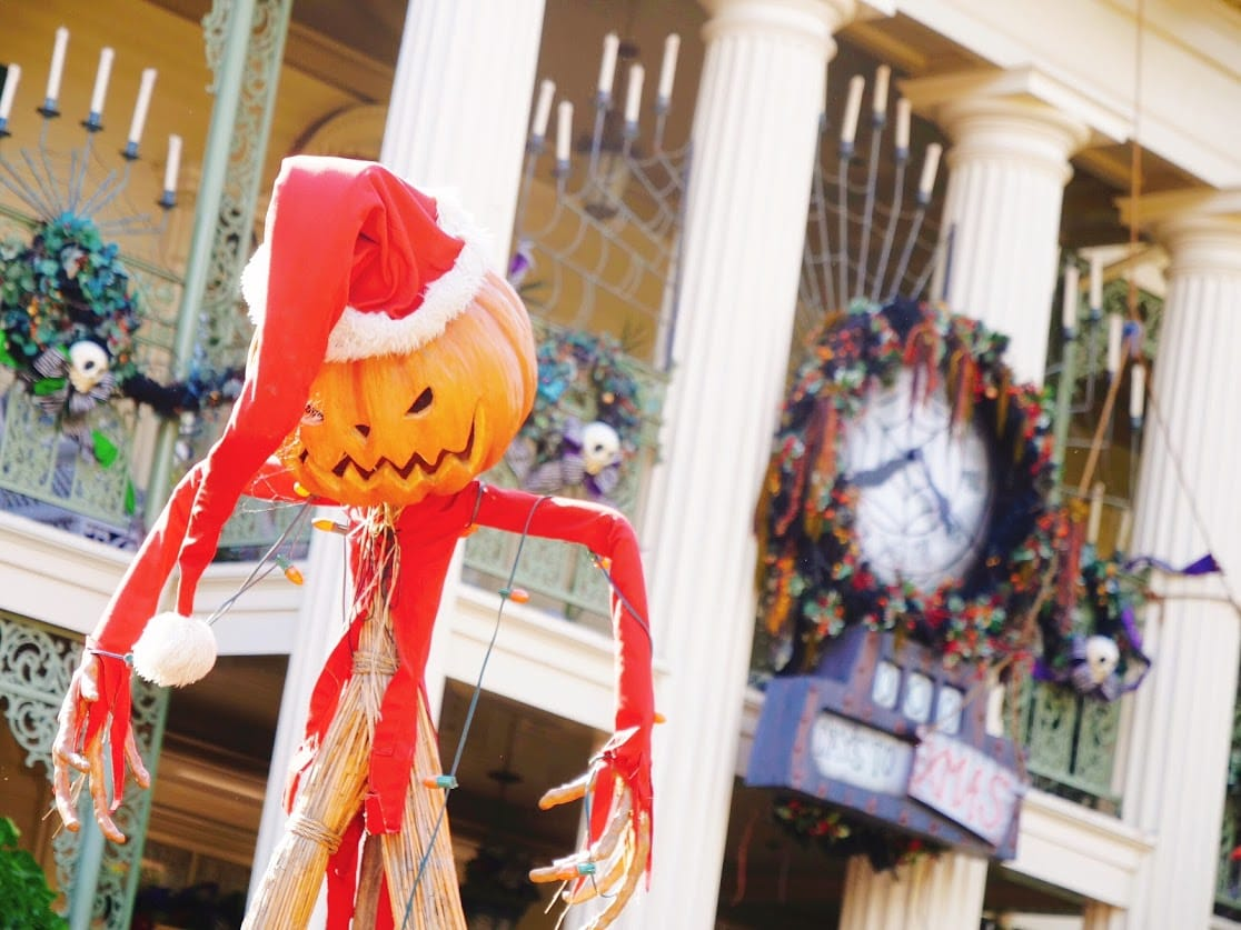 Jack the Pumpkin King in a Santa hat in front of Haunted Mansion Holiday for Christmas at Disneyland.