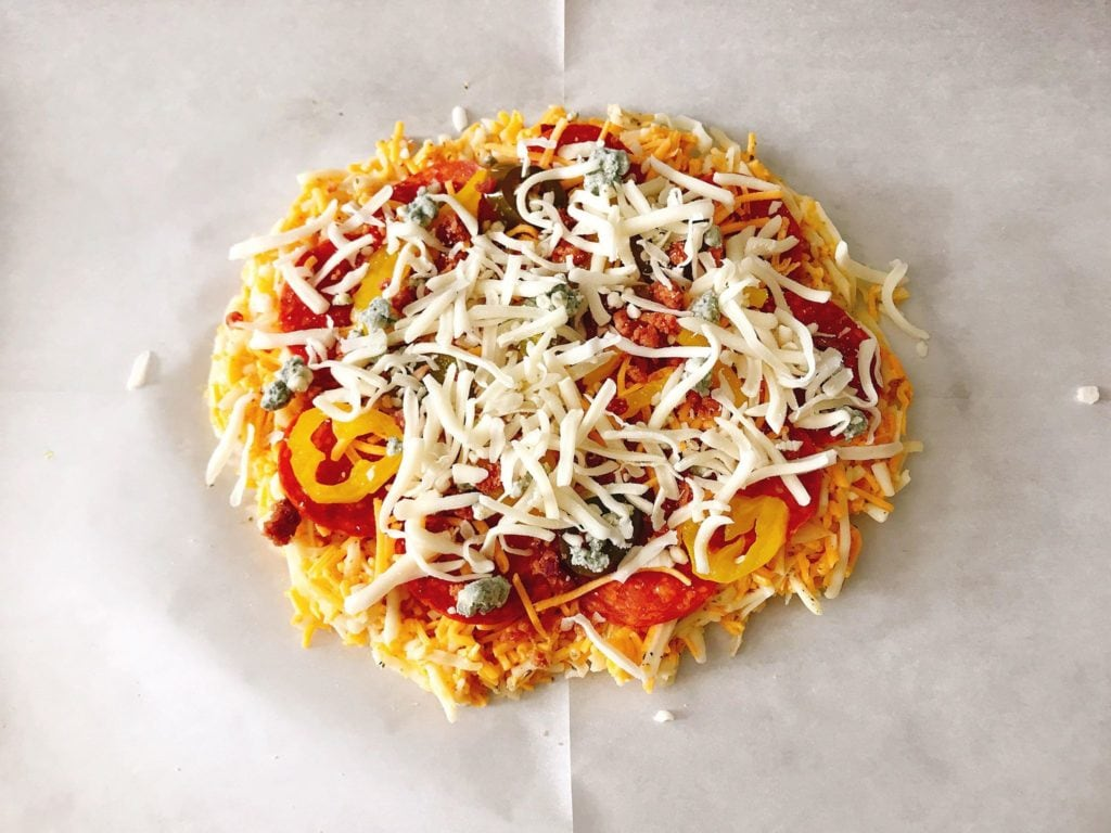 Pepperoni, peppers and other toppings topped with shredded mozzarella on Keto Pizza.
