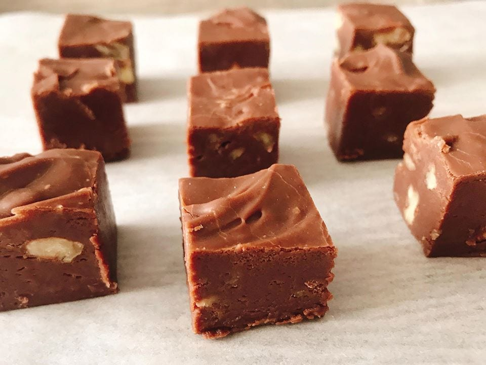 Squares of easy homemade fudge recipe lined up on parchment paper.