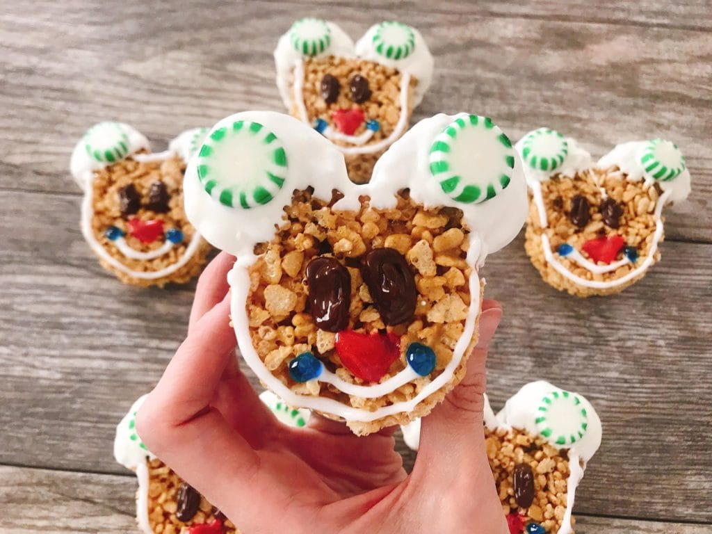 A hand holding up a decorated Mickey Mouse Gingerbread Rice Krispie Treat.