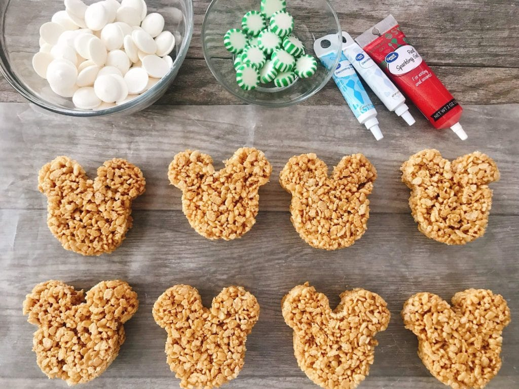 A bowl of marshmallows, a bowl of green starlight mints, decorating gel, and 8 Mickey Mouse shaped Gingerbread Rice Krispie Treats.
