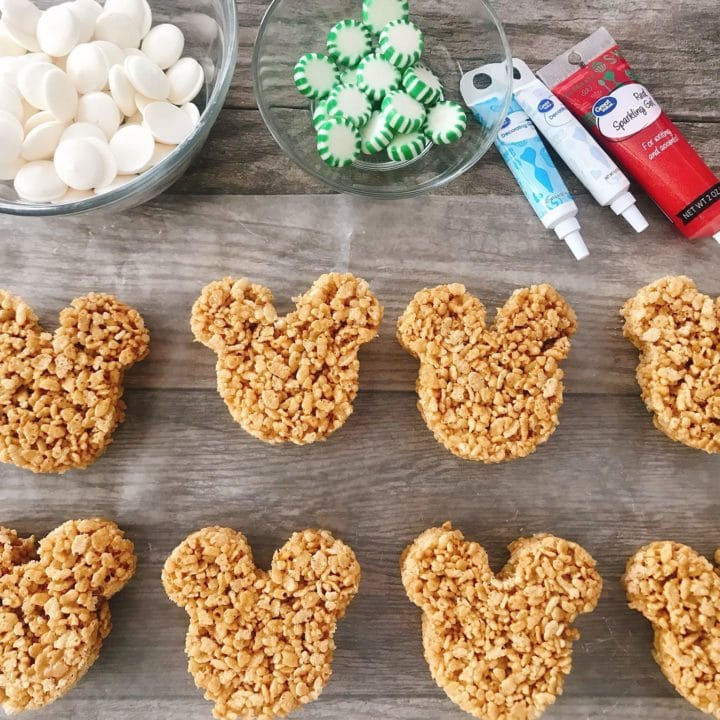 Eight Mickey Mouse shaped Gingerbread Rice Krispie Treats, decorating gel, a bowl of Christmas Mints, and a bowl of white chocolate.