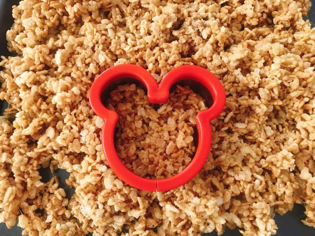 A pan of warm Gingerbread Rice Krispie Treats with a Mickey Mouse cookie cutter.
