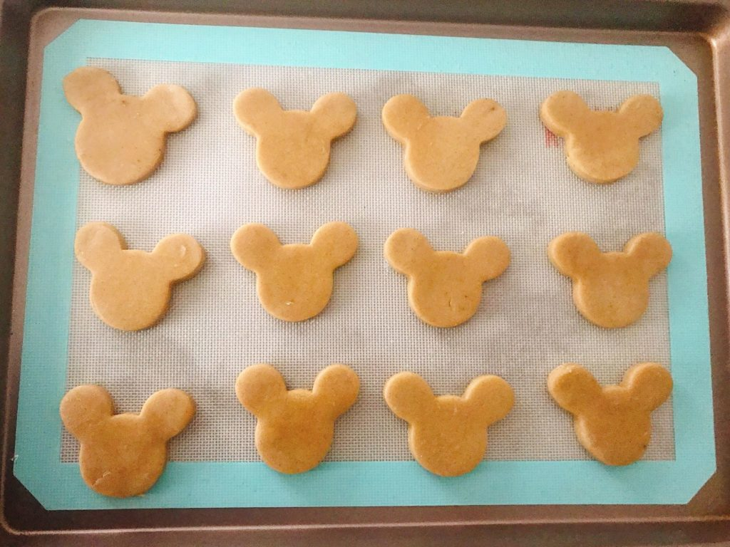 Unbaked gingerbread sugar cookies shaped like Mickey Mouse on a baking sheet.