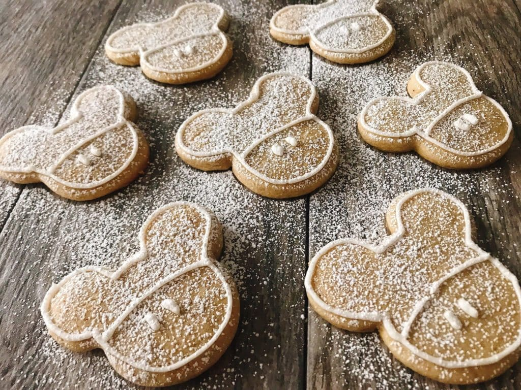 Mickey Mouse shaped gingerbread sugar cookies dusted with powdered sugar on a wooden background.