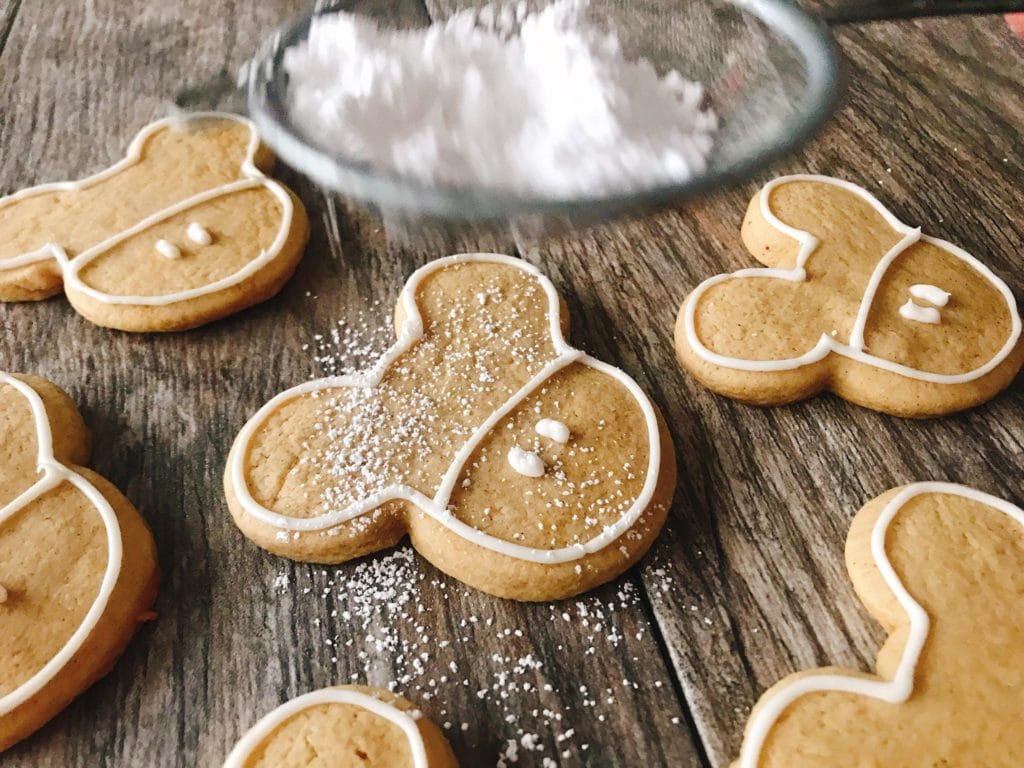 Powdered sugar being dusted on gingerbread sugar cookies.
