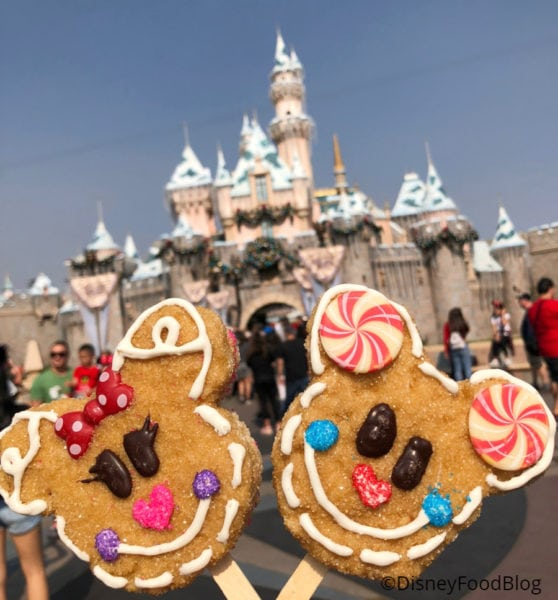 A Mickey Mouse and Minnie Mouse shaped Gingerbread Rice Krispie Treat in front of Sleeping Beauty Castle at Disneyland.