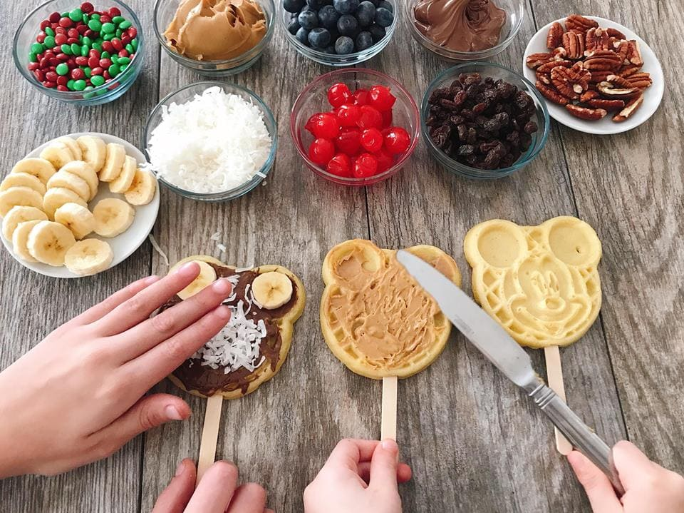 Waffle bar toppings in bowls, two kids adding toppings to Mickey Waffles to make a Mickey Mouse Waffle Bar