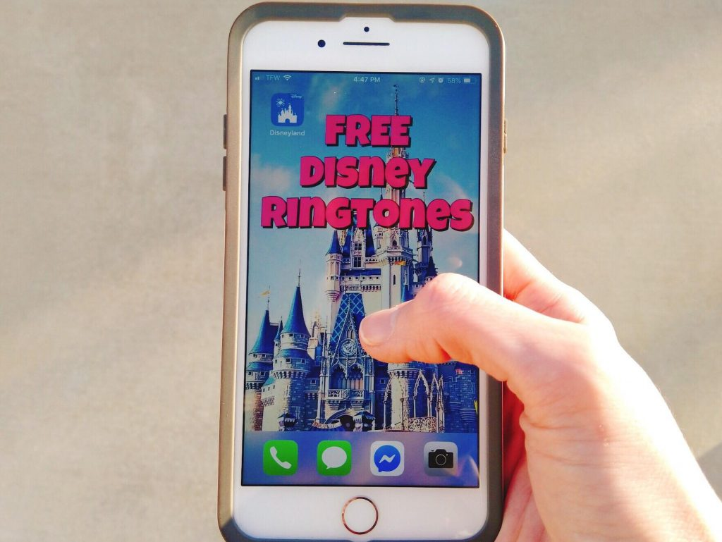 "A hand holding an phone with a picture of Cinderella's castle and the words ""Free Disney Ringtones""."