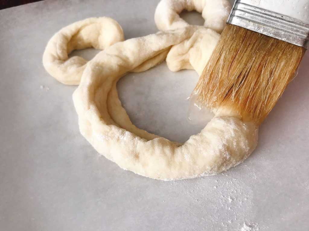 A brush on an unbaked Mickey Pretzel