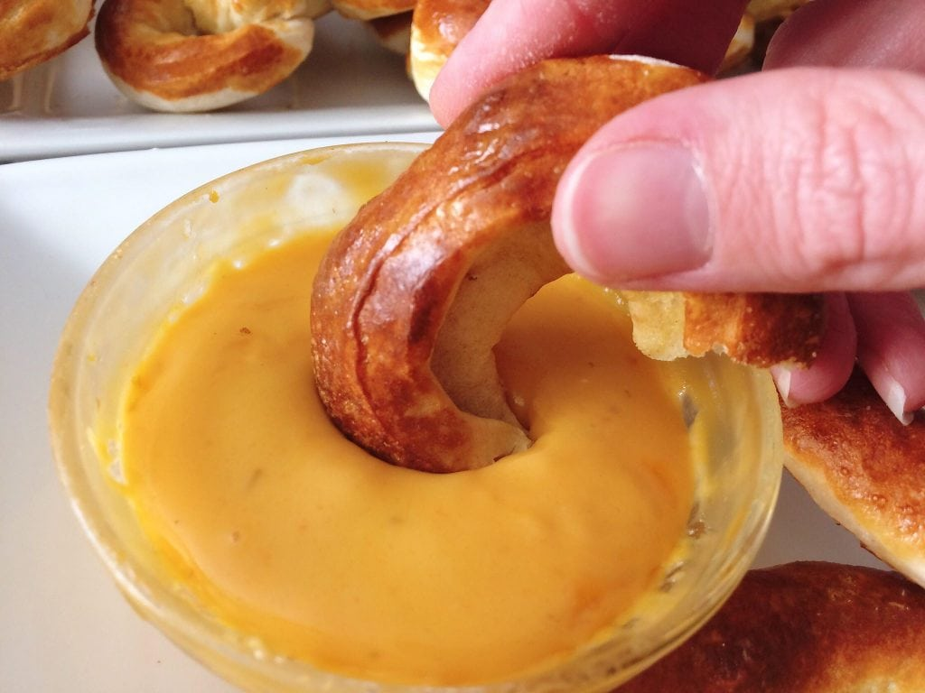 A soft Mickey Pretzel being dipped in cheese sauce.