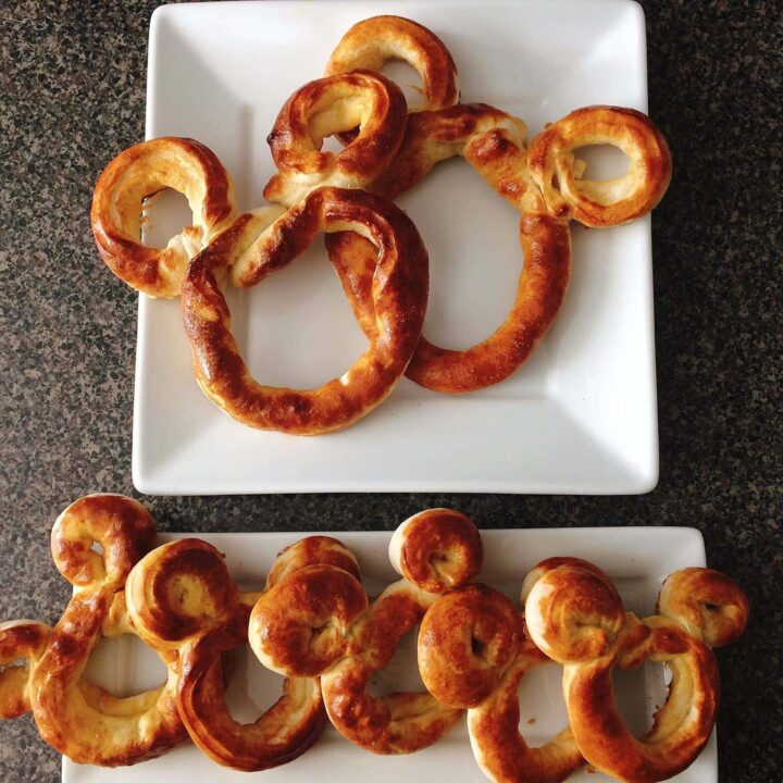 Large and small Mickey shaped soft pretzels displayed on white plates.