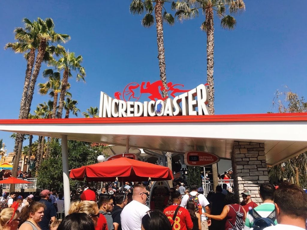 People standing in line in front of the Incredicoaster sign and palm trees at Disney California Adventure.