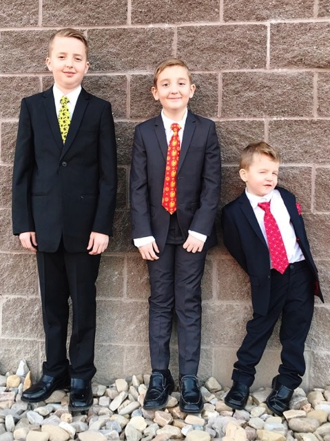 Three boys dressed in super hero themed suits.