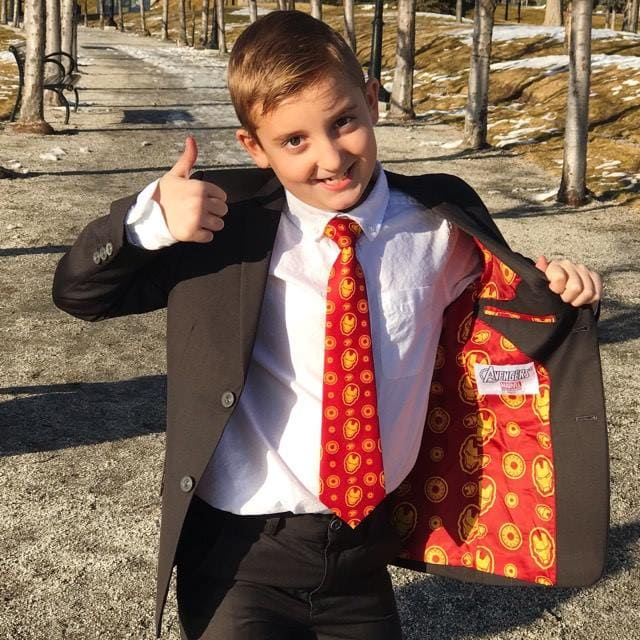 A boy wearing an Iron-Man themed suit giving a thumbs up.