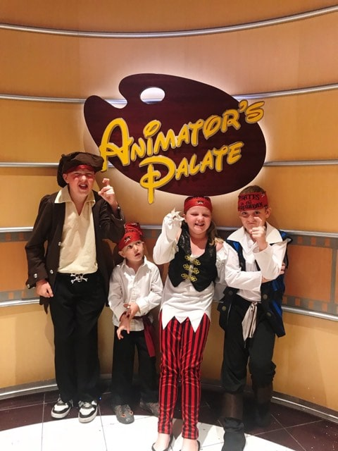 Kids dressed up as pirates in front of the Animator's Palate sign on a Disney Cruise.