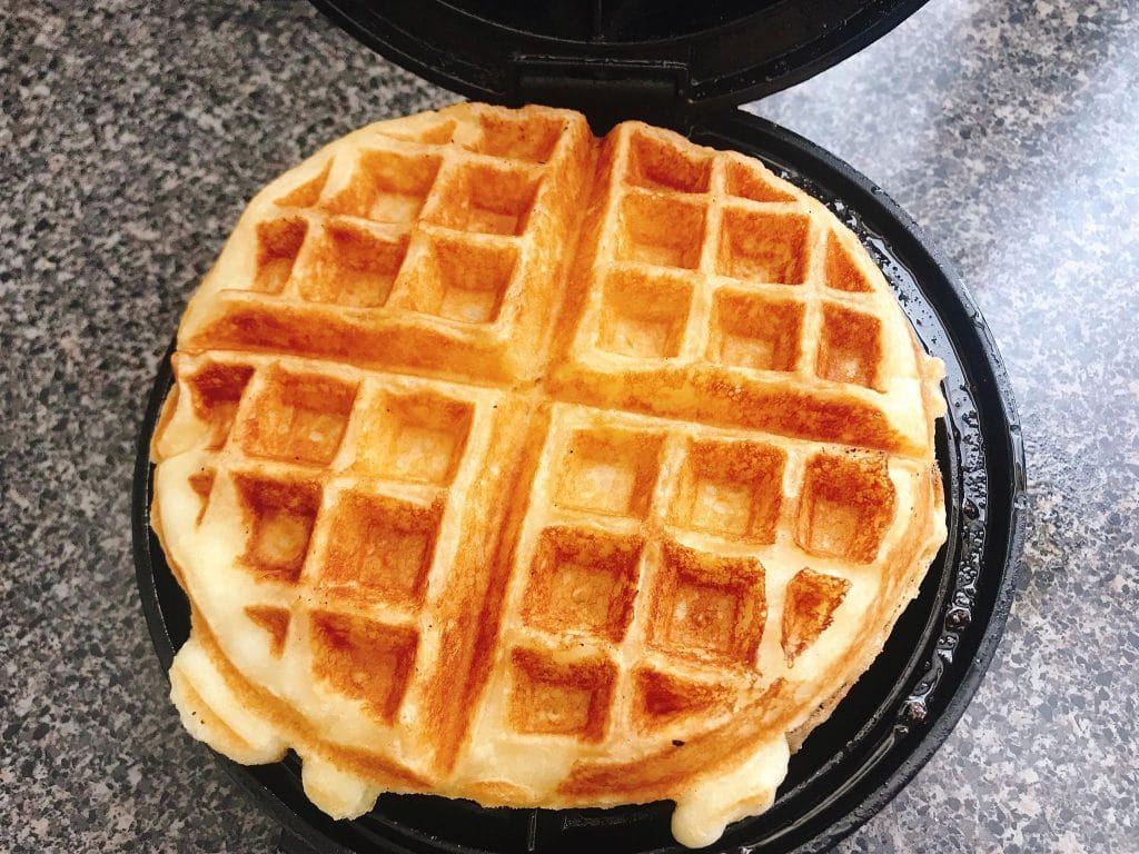 A golden brown sweet cream waffle on a waffle iron.