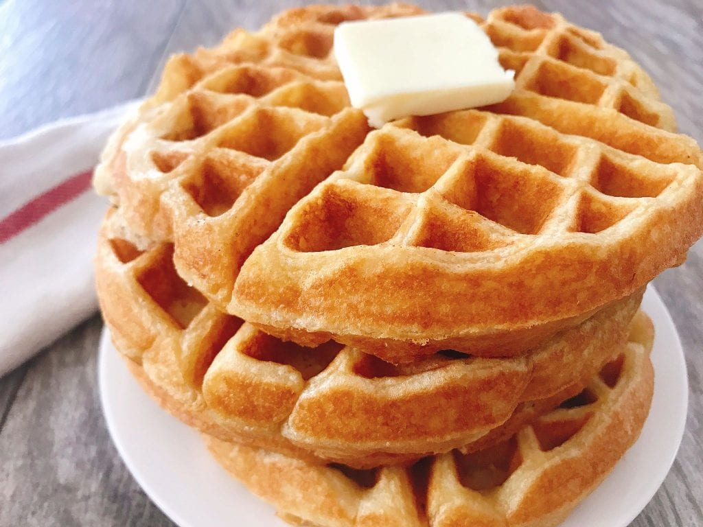 A stack of sweet cream waffles on a plate with a pat of butter.