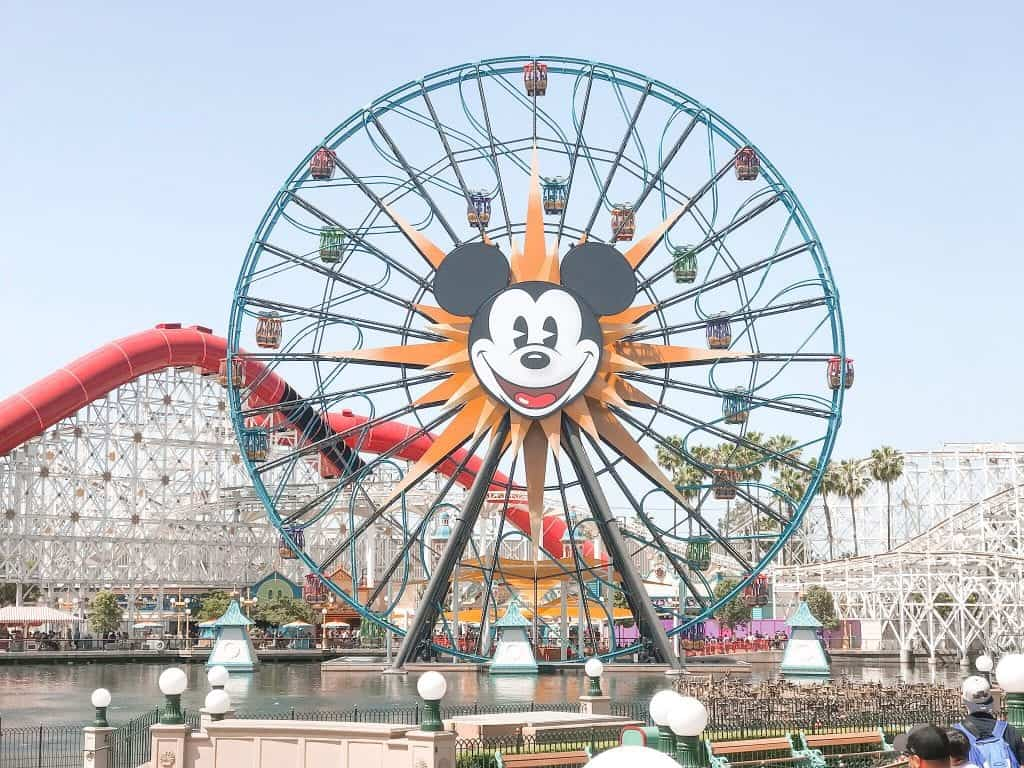 Mickey Mouse face on a Ferris wheel in front of a white roller coaster at Disneyland.
