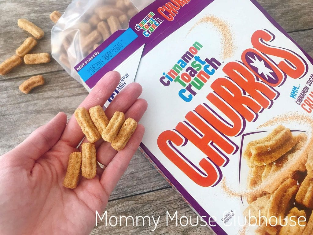 A handful of Cinnamon Toast Crunch Churros over a box of them.