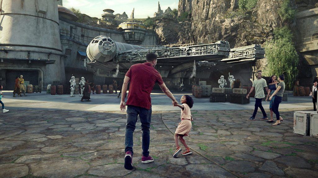 A dad and his daughter holding hands in front of Star Wars: Galaxy's Edge the new Star Wars Land in Disneyland and Walt Disney World.