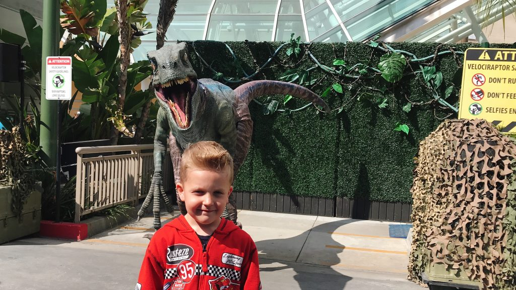 A boy standing in front of a robotic velociraptor at Universal Studios Hollywood.