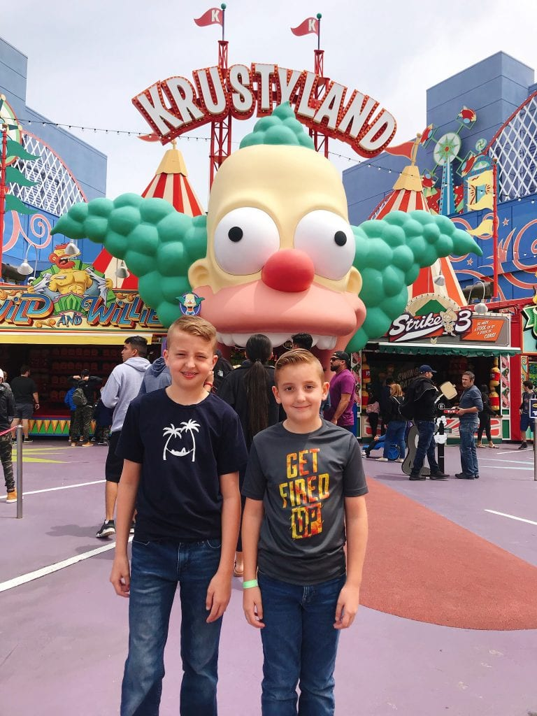 "Two kids standing in front of a large clown with a sign that says ""Krustyland"""