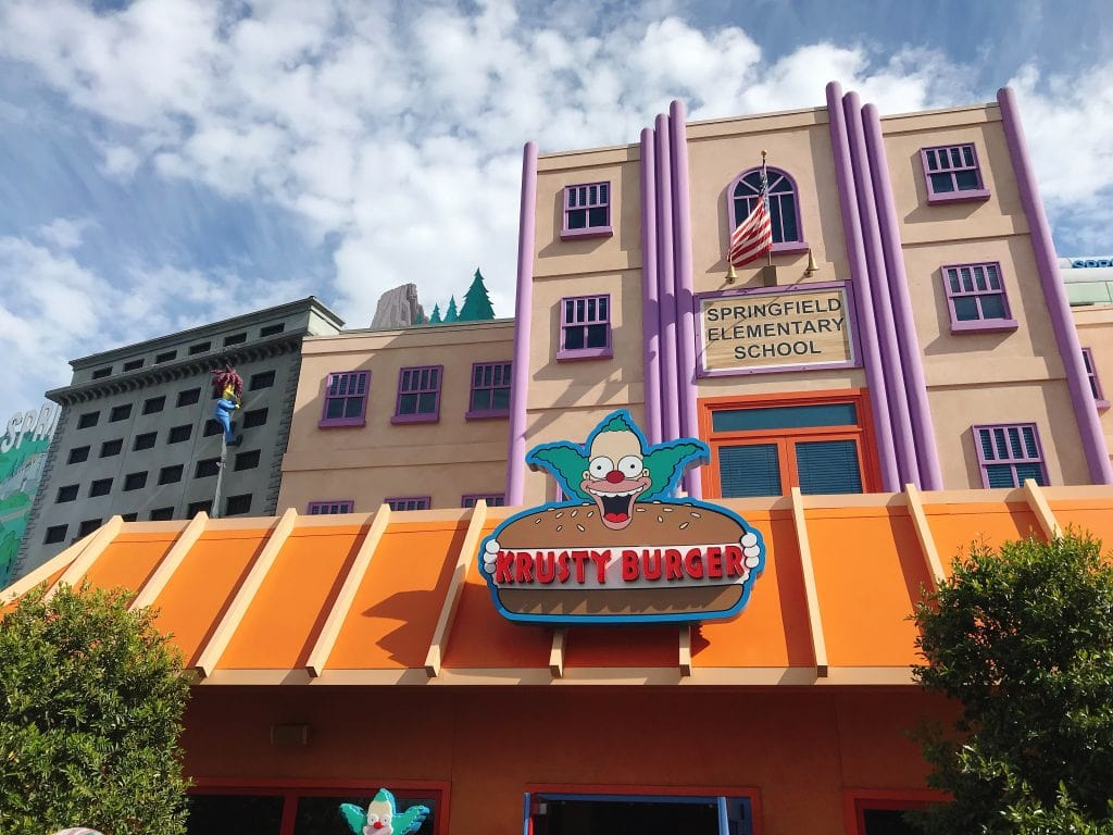 "A building with a clown holding a hamburger that says, ""Krusty Burger"""