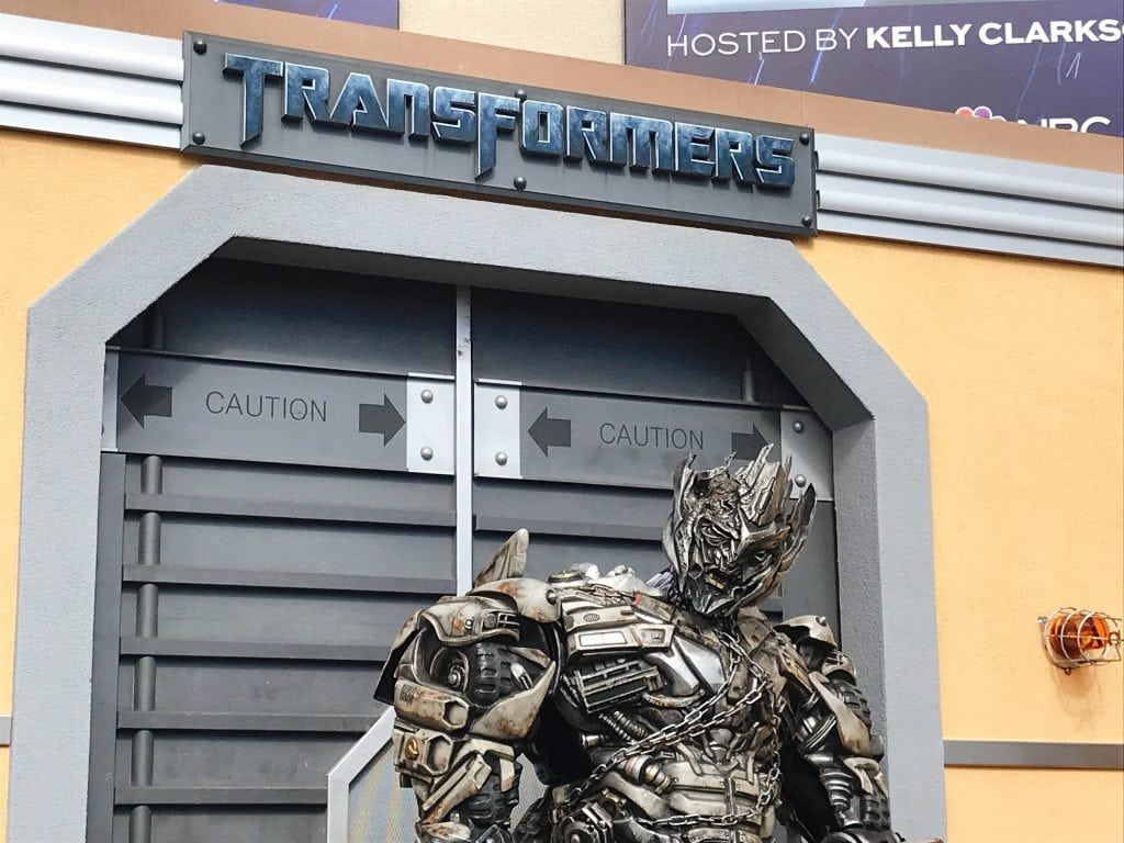 "A large Transformer in front of metal doors with a sign that says ""Transformers"""